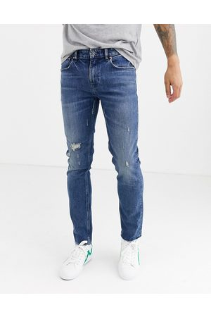 ASOS DESIGN Muži Skinny - Cone Mill Denim skinny 'American classic' jeans in mid wash blue with abrasions and raw hem