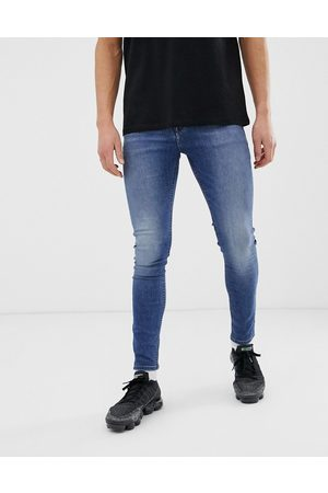 ASOS Spray on jeans in power stretch denim in mid wash blue