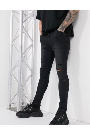 ASOS Spray on jeans in power stretch with heavy rips in washed black