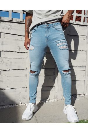 ASOS Spray on 'vintage look' jeans with power stretch in light wash blue with heavy rips
