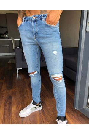 ASOS Spray on'vintage look' jeans with power stretch in mid wash blue with knee rips