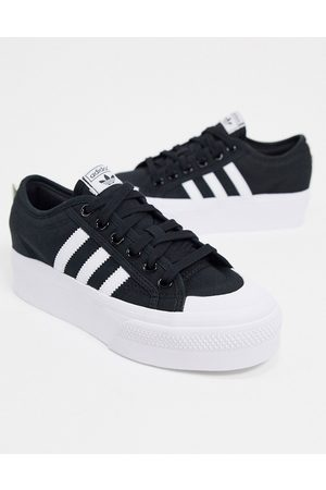 adidas Nizza platform trainers in black and white