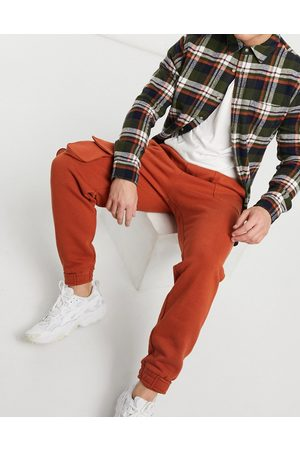 ASOS Tapered joggers with multi utility pockets & tab cuffs in burnt red-Brown