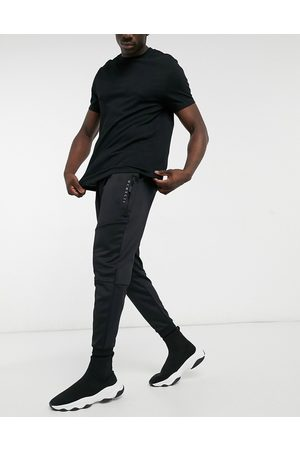 ASOS Tapered joggers in spongey fabric in black with roman numerals