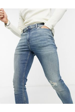 ASOS Super skinny jeans in vintage mid wash blue with knee rip and abrasions