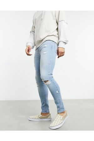 ASOS Spray on jeans with power stretch in vintage light wash with heavy rips-Blue