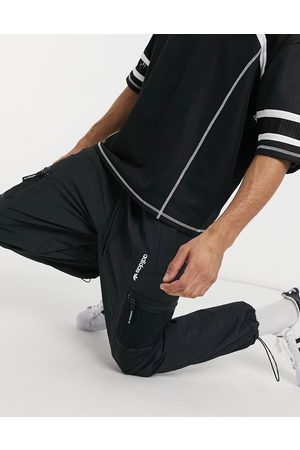 adidas Adventure woven joggers with pocket detail in black