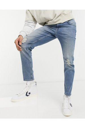 ASOS Stretch tapered jeans in mid wash with knee rips-Blue