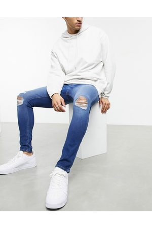 ASOS Spray on jeans in power stretch with 'less thirsty' wash in mid blue with knee rips