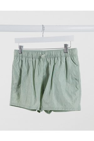 ASOS Swim shorts in crinkle texture with toggle fastening in short length-Green