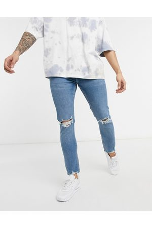 Bershka Super skinny fit jeans with rips in mid wash blue