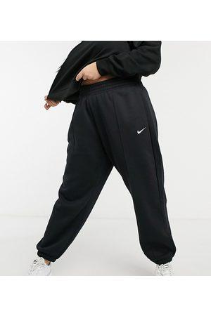 Nike Plus mini swoosh oversized jogger in black