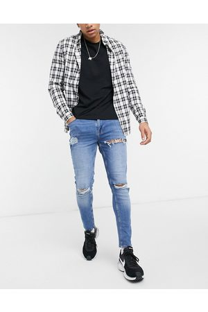 ASOS DESIGN Skinny jeans in mid wash blue with heavy rips
