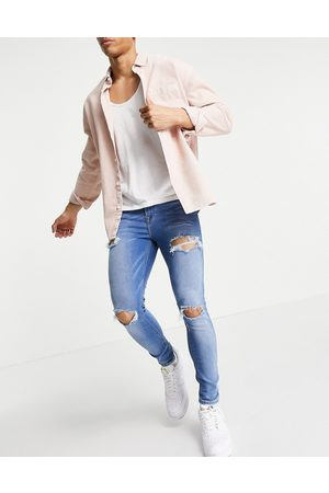 ASOS Spray on jeans with power stretch in mid wash blue with heavy rips