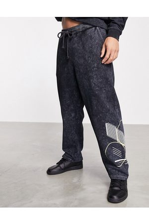 ASOS Muži Tepláky - Co-ord relaxed joggers with acid wash & pigment print-Black