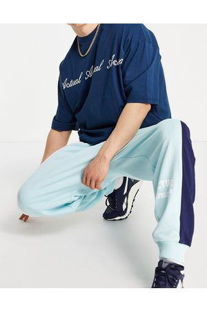 ASOS Muži Tepláky - Co-ord oversized joggers with colourblock cut and sew detailing and logo print in blue