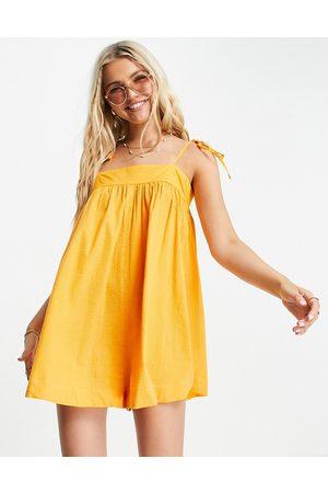 ASOS DESIGN Tie shoulder seersucker swing playsuit in mimosa orange