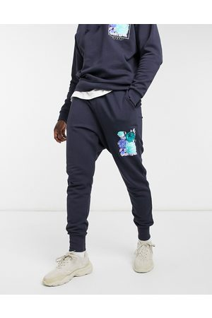 ASOS DESIGN Muži Tepláky - Co-ord skinny joggers with rib insert and flower logo graphic-Navy