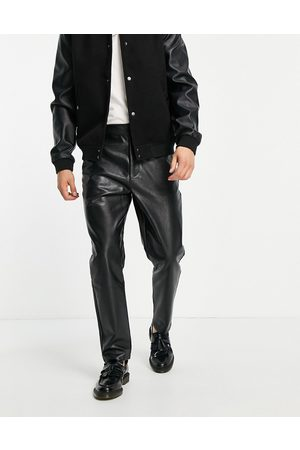 ASOS Tapered trousers in faux leather in black