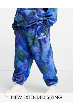 ASOS Muži Tepláky - ASOS Daysocial relaxed joggers in teddy borg with all over print blue tie dye
